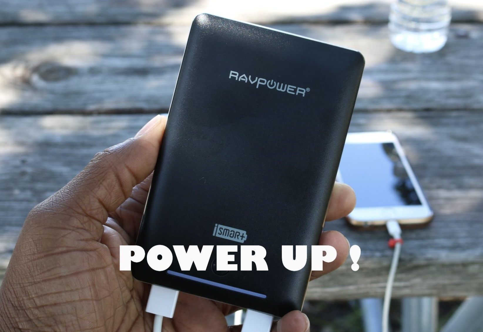 Reviewer holding the power bank in their hand while it charges a phone