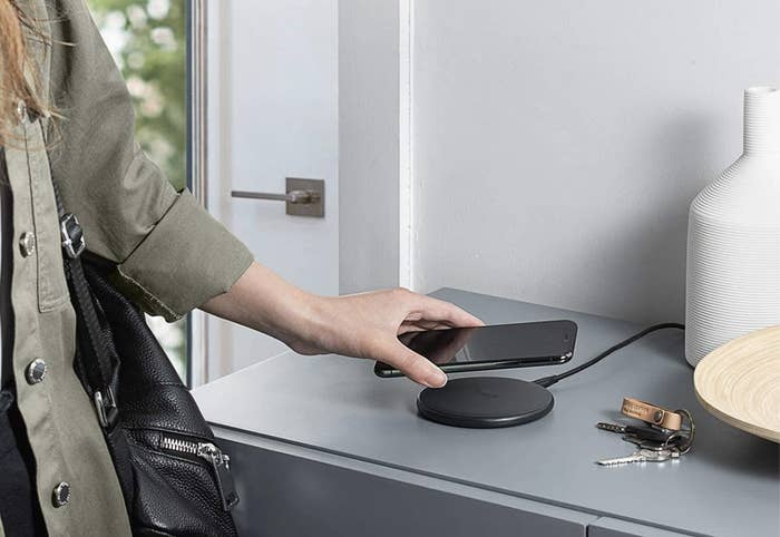 A model placing a phone down on a wireless black charging pad