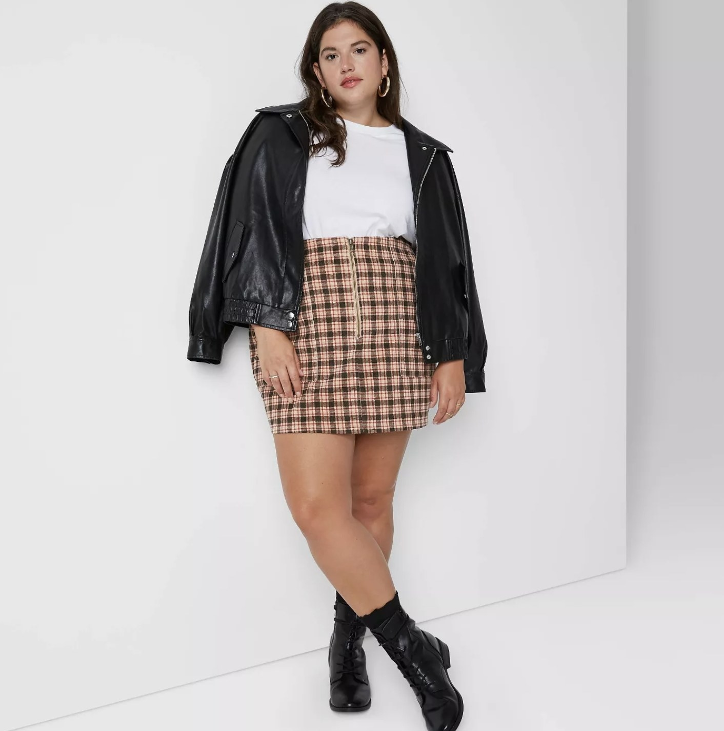 Model is wearing a brown and black plaid zip-front corduroy skirt