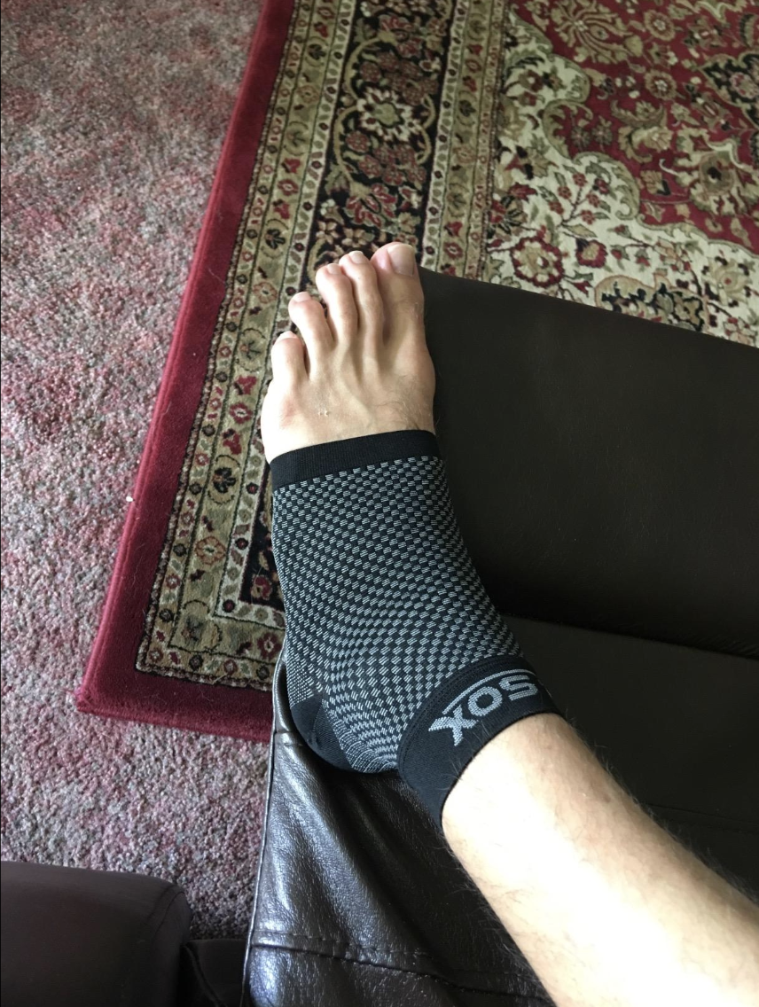 Reviewer in a black compression sock that covers from the bottom of the toes to the top of the ankle