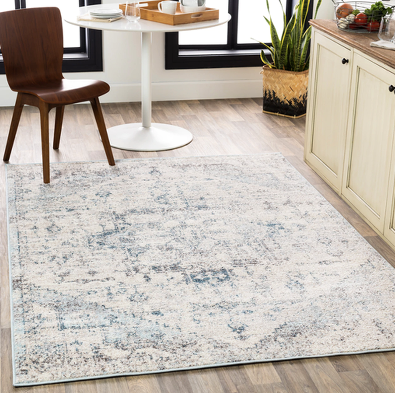 A square shaped white rug with a light blue diamond design and spots of blue and gray