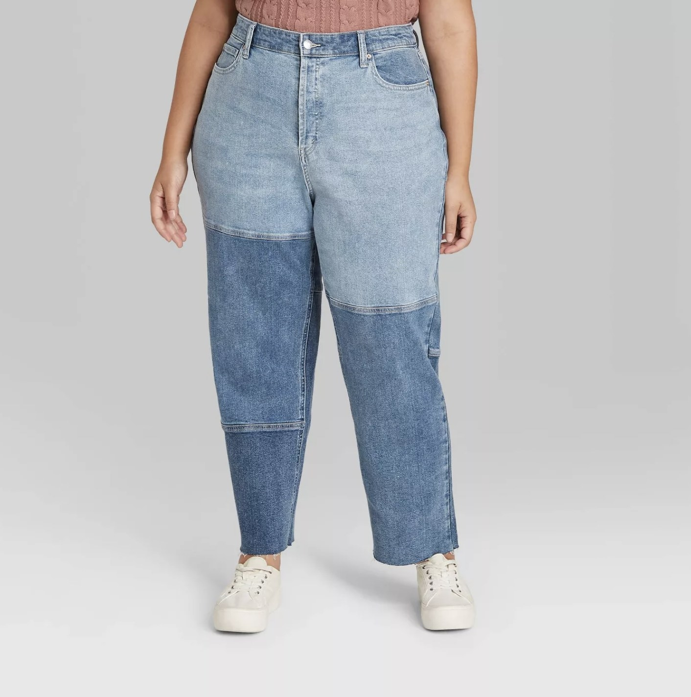 Model is wearing a pair of light-wash patchwork denim mom jeans