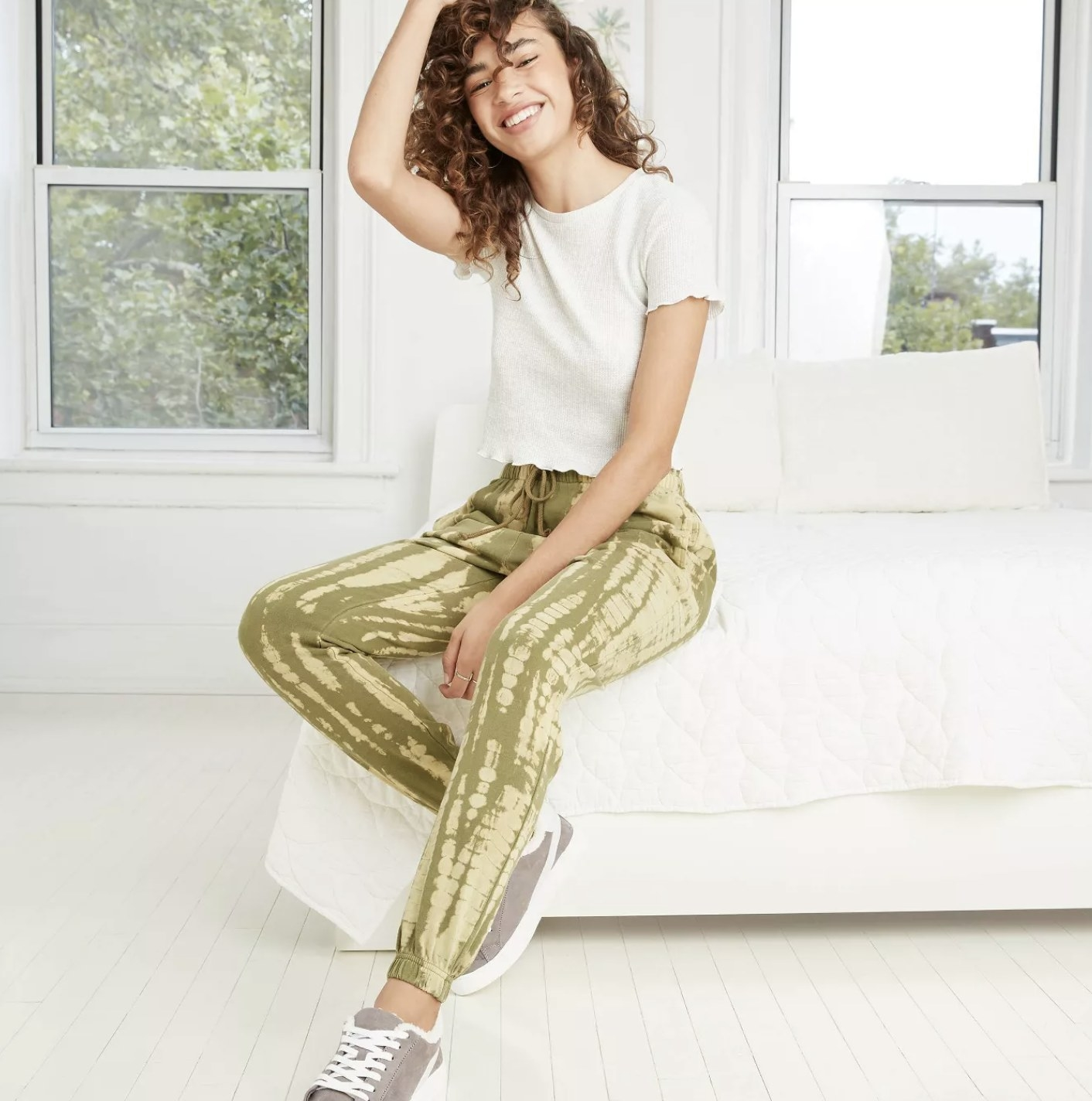 Model is wearing an green acid-wash patterned pair of joggers