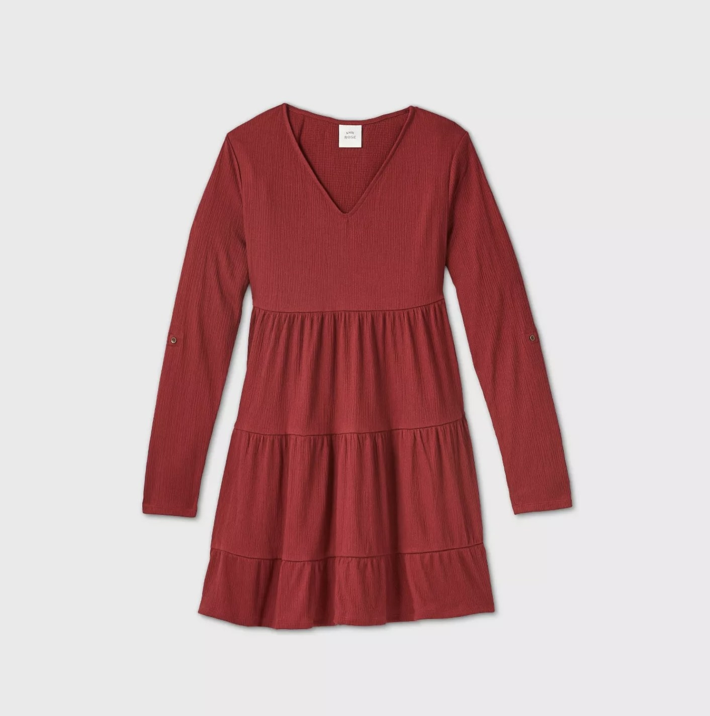 A burnt red tiered midi dress with long sleeves and a v-neckline