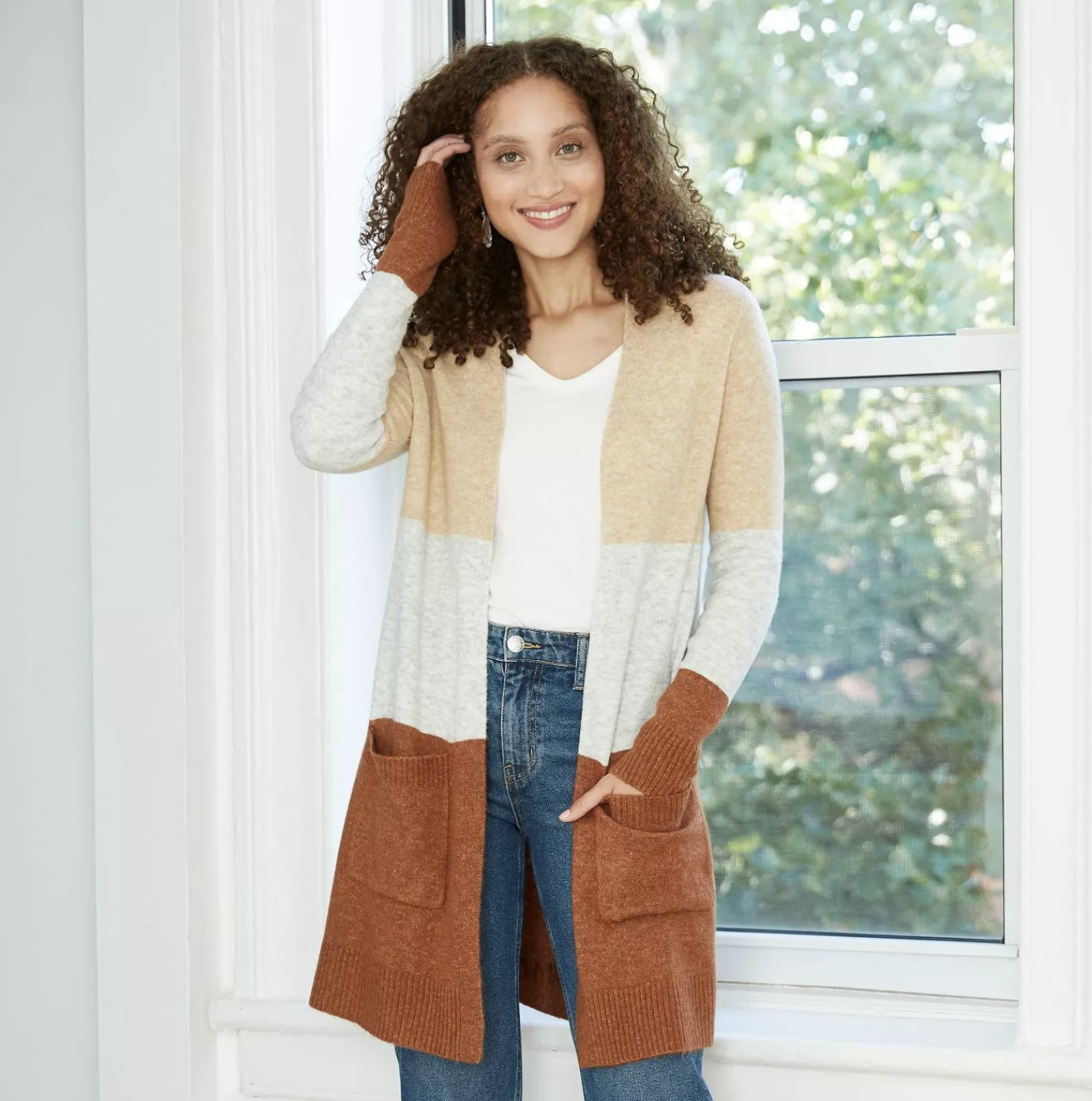 Model is wearing a burnt orange, cream, and beige color block cardigan