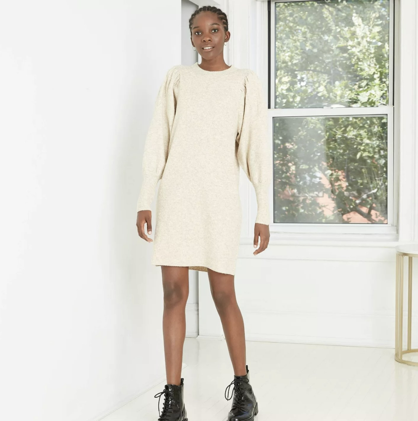 Model is wearing a cream sweater dress with puffed long sleeves