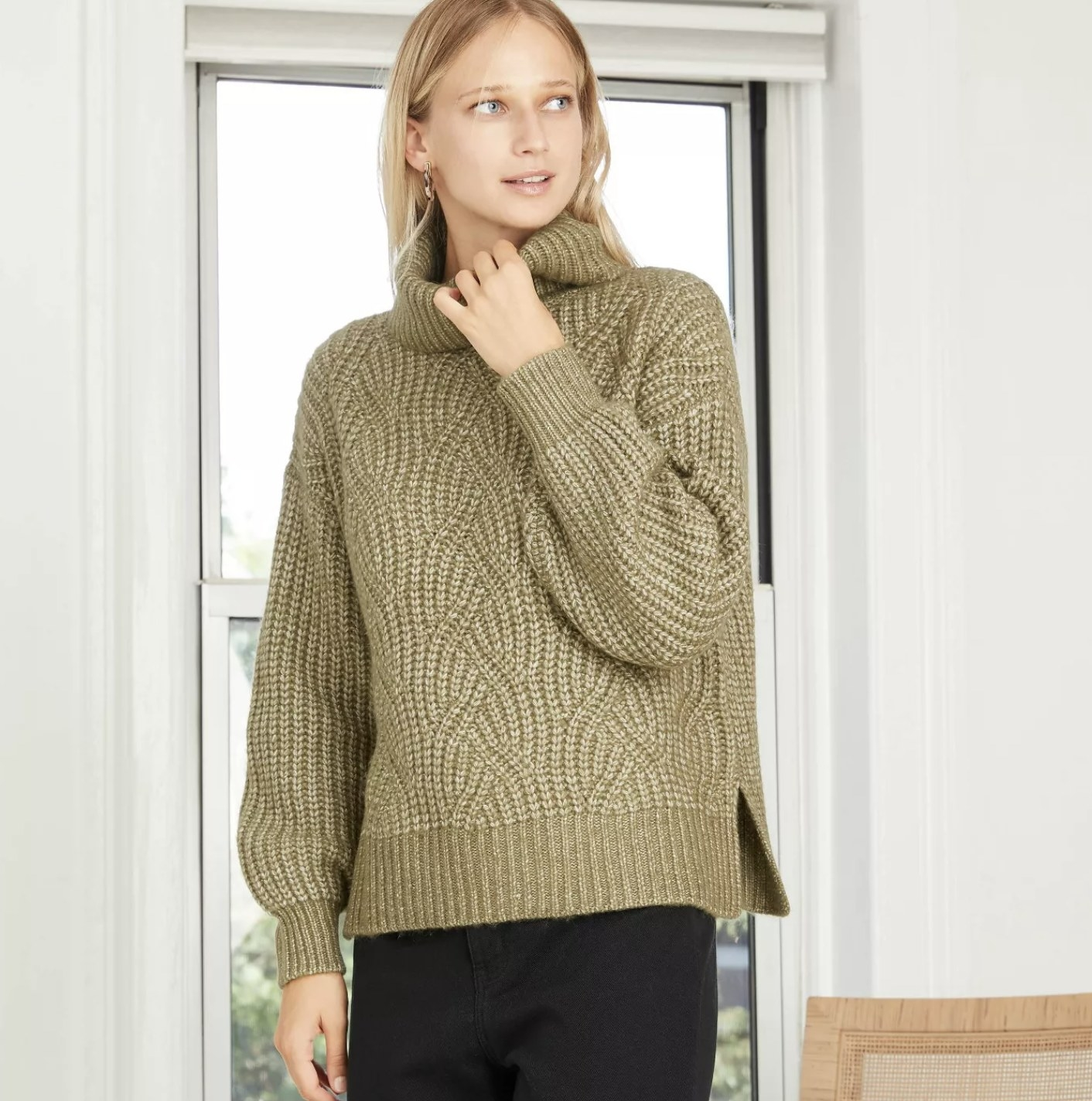Model is wearing an olive green cable stitched turtleneck sweater with side slits