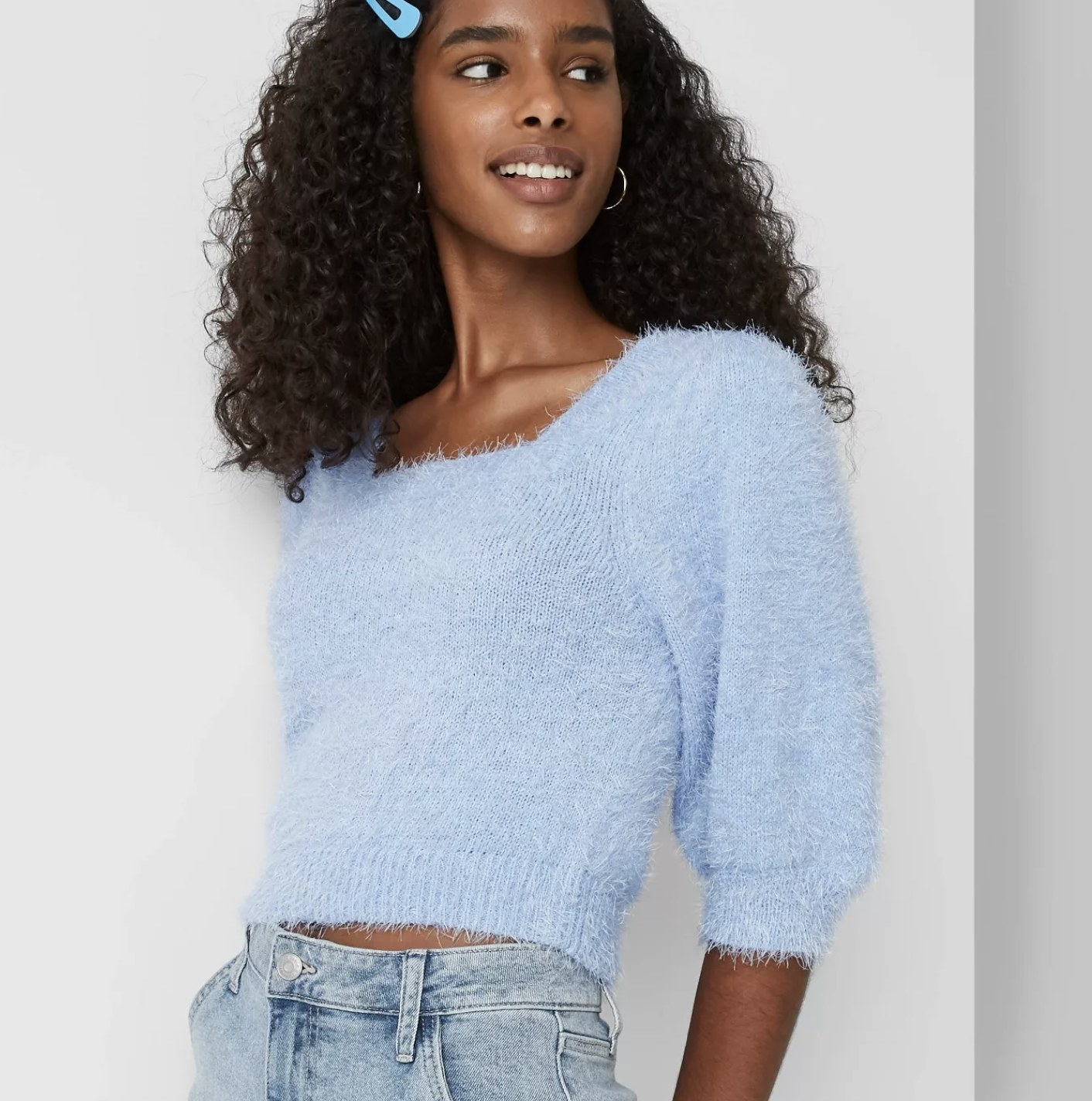 Model is wearing a light blue fuzzy cropped sweater with a square neckline