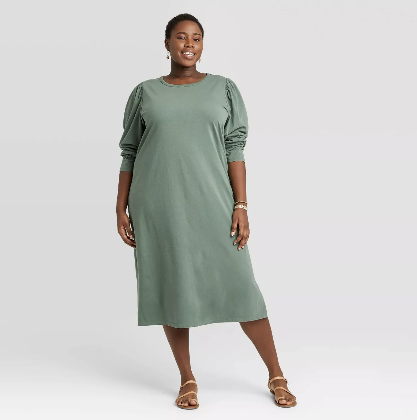 Model is wearing a muted green long puff sleeve midi dress