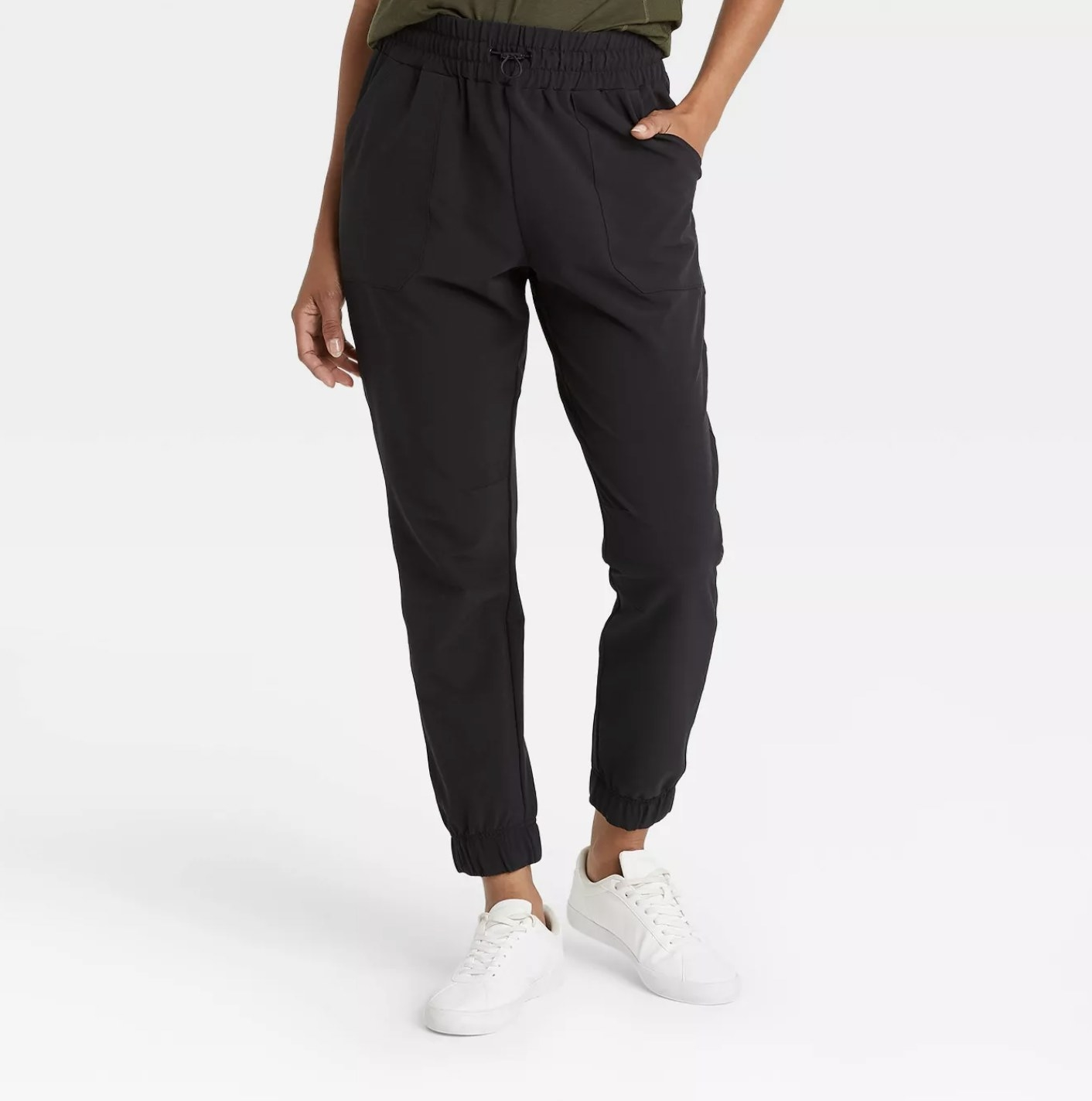 Model is wearing black ankle-length joggers