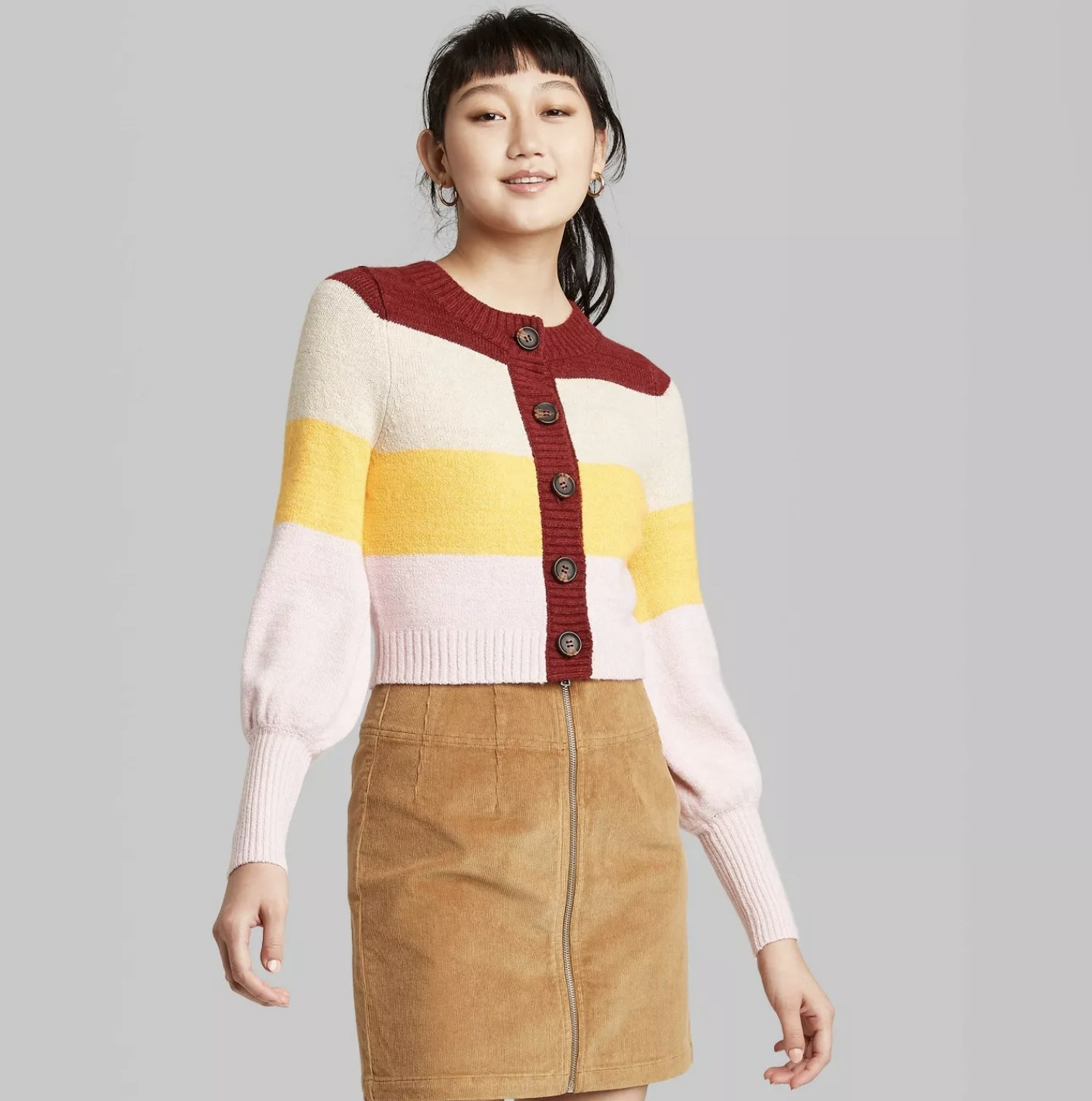 Model is wearing a striped button front cardigan with yellow, cream, red, and pink colors and puff sleeves