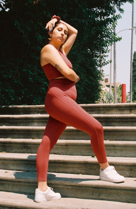 Model wears terra red high-rise compressive leggings with matching sports bra top