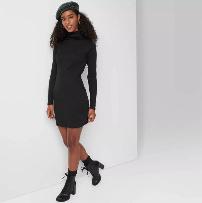 Model wearing black body-con dress with chunky boots and a beret