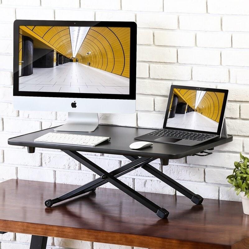 a black adjustable standing desk converter holding a desktop, ipad, keyboard, and mouse