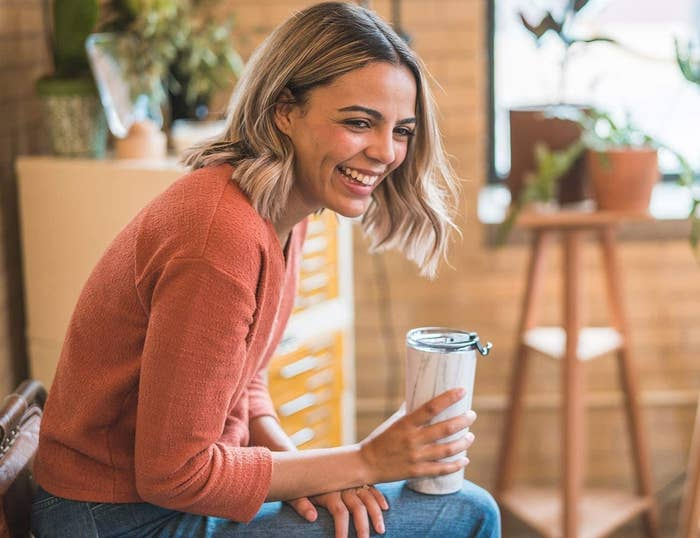 A smiling person holds the tumbler on their lap