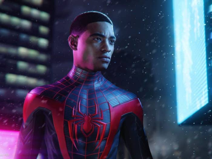 A young man in a black Spider-Man suit stares intently.