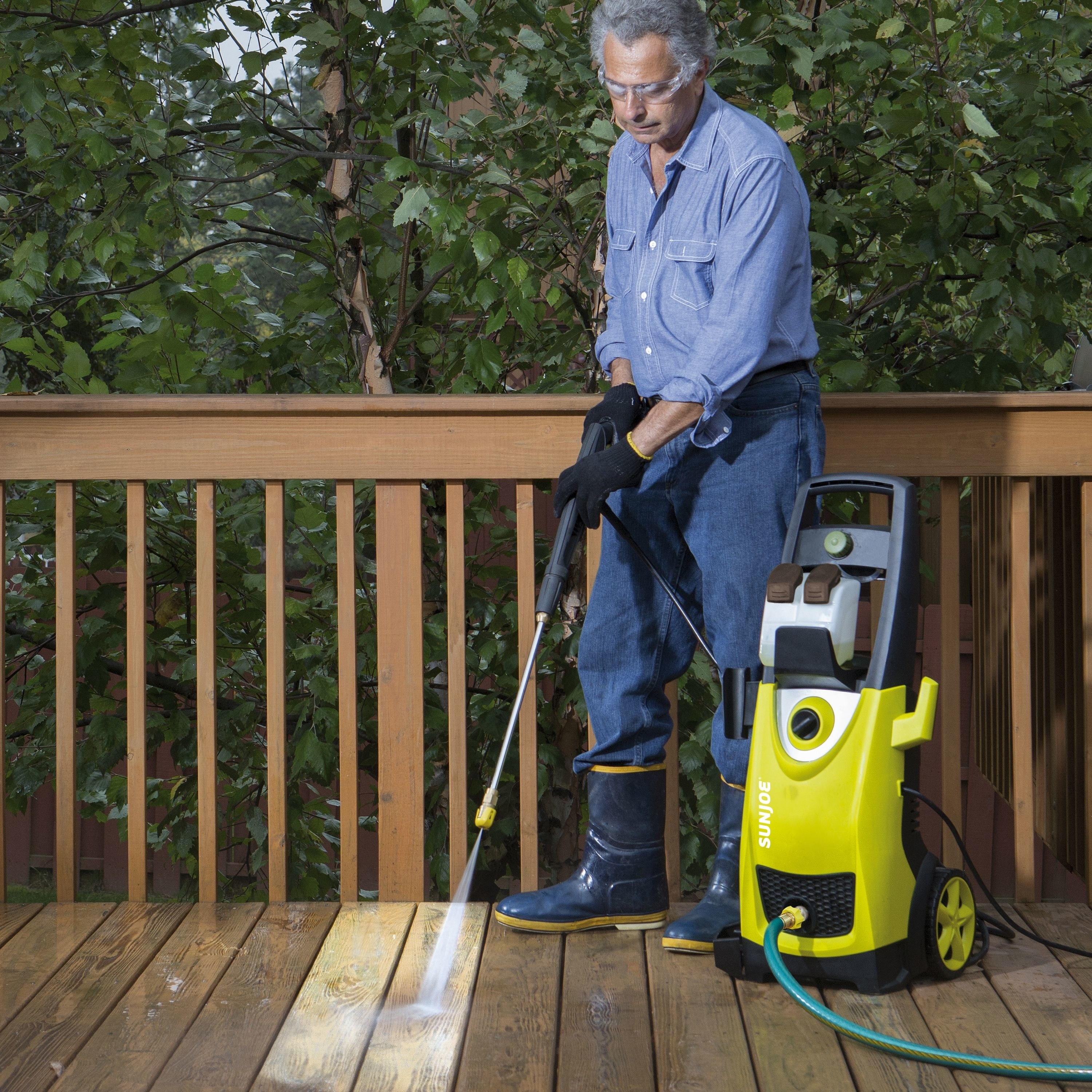 person using a pressure washer to clean the back deck