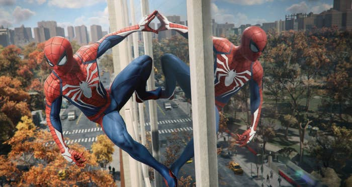 Spider-Man looks down at the city sticking to a window on a skyscrper.