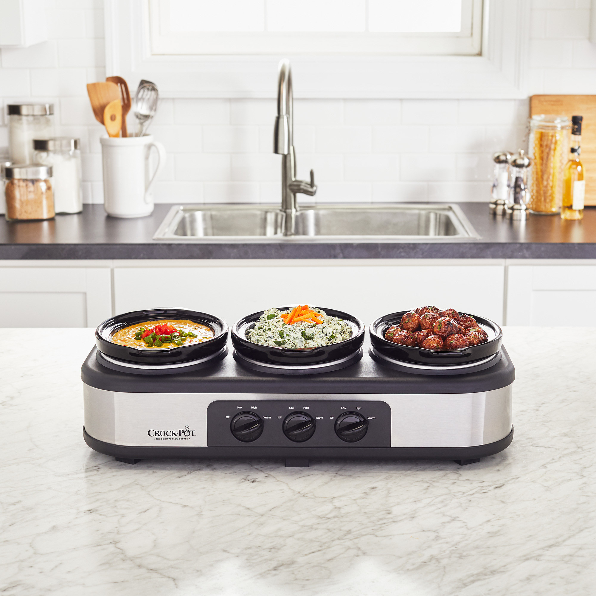 trio slow cooker on a kitchen counter with appetizers in it