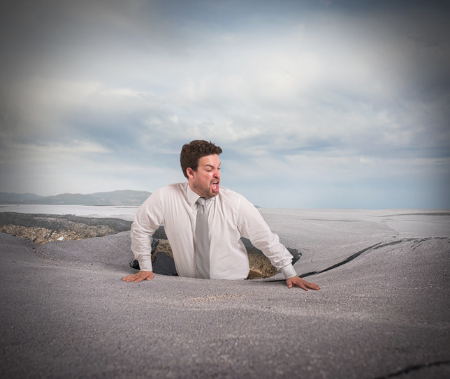 man in suit getting swallowed by quicksand