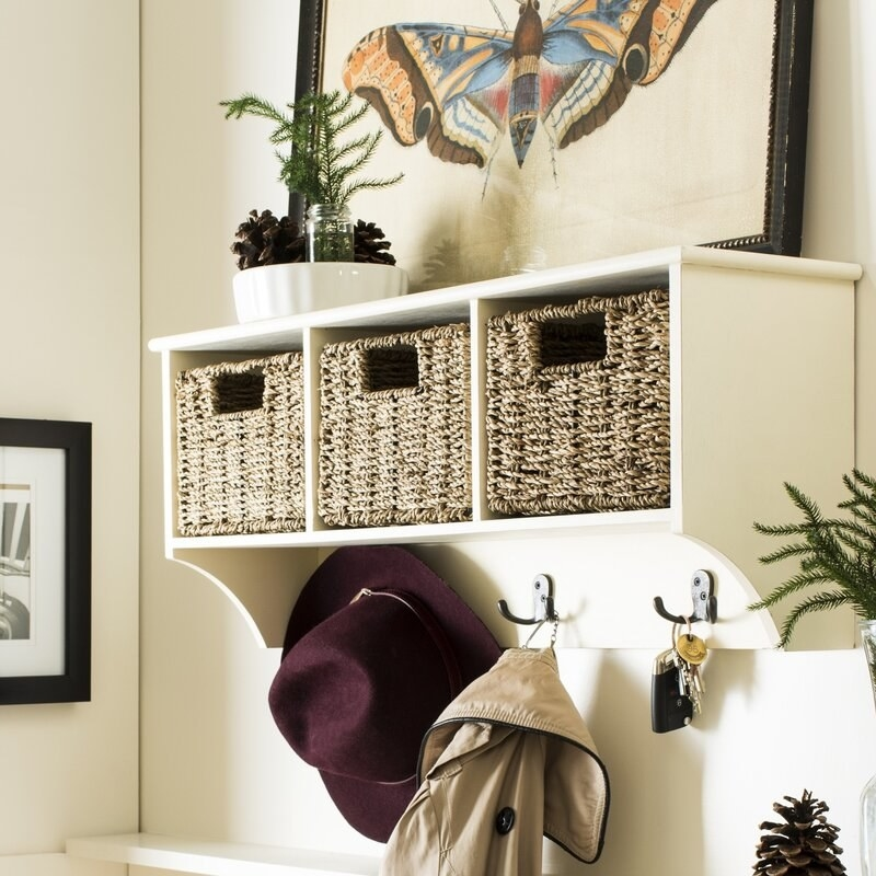 A wall hook with shelves and three wicker baskets, holding keys, a jacket, and a hat