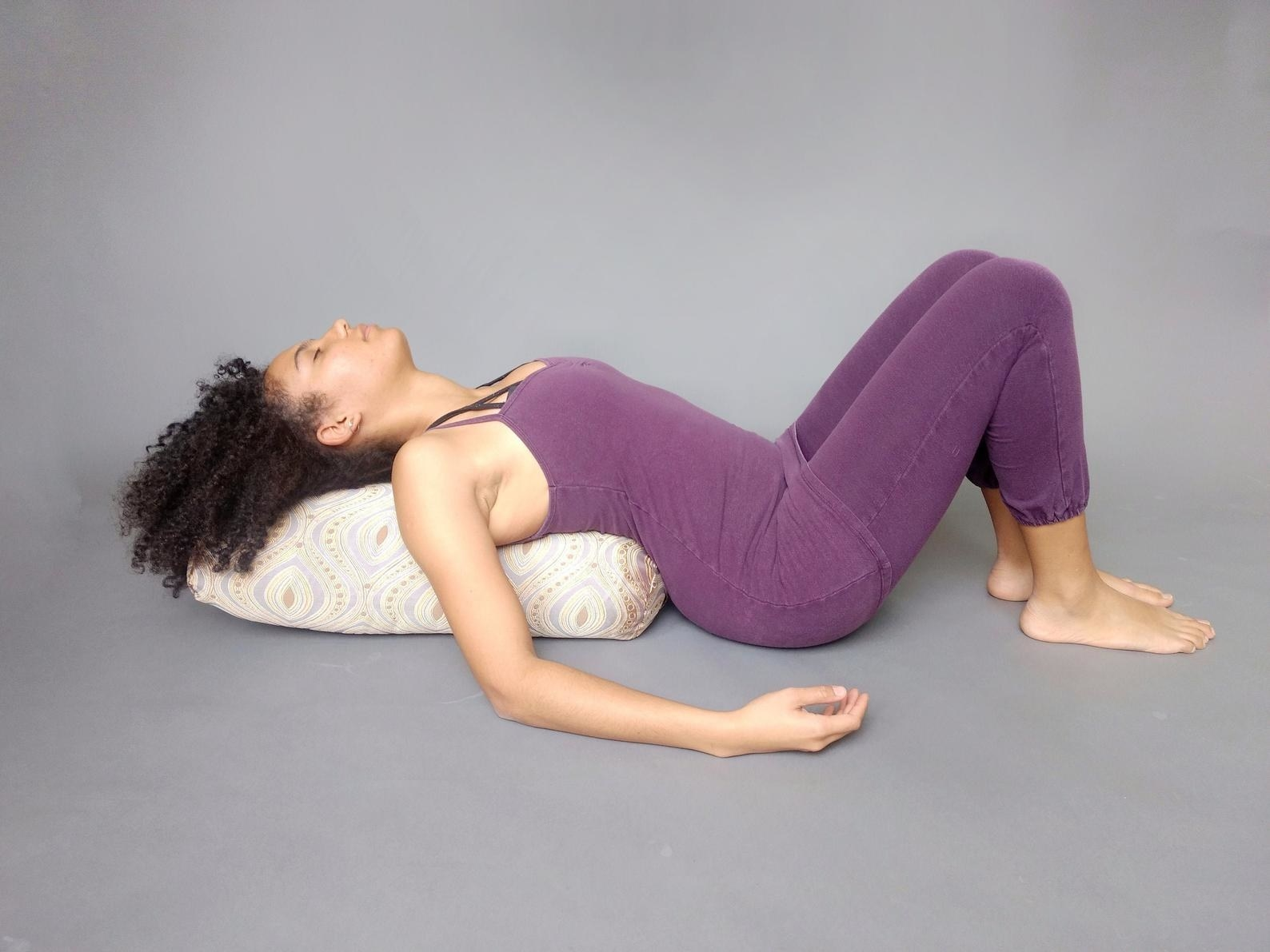 A model with the long rounded-end pillow on their back and head, supporting them while lying down