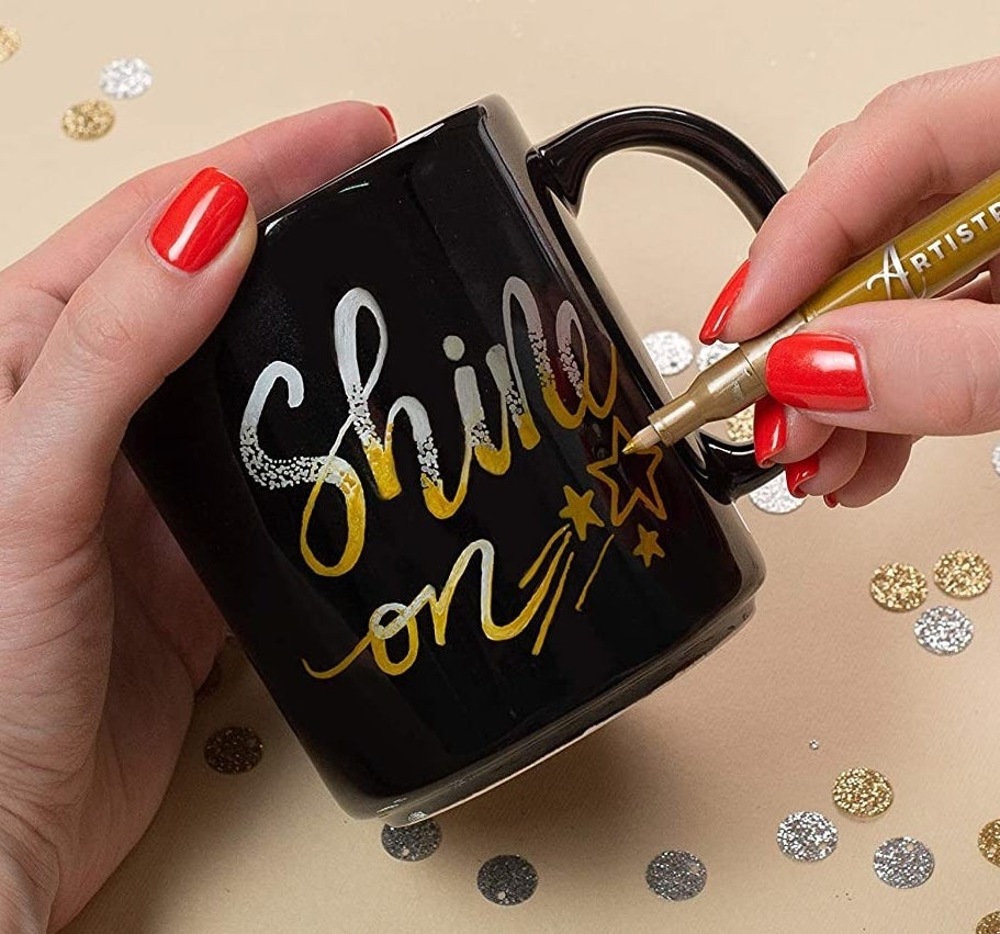 A person writes on a mug using the metallic marker
