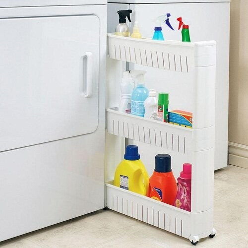 a narrow while sliding storage rack in between a washer and dryer, holding detergent