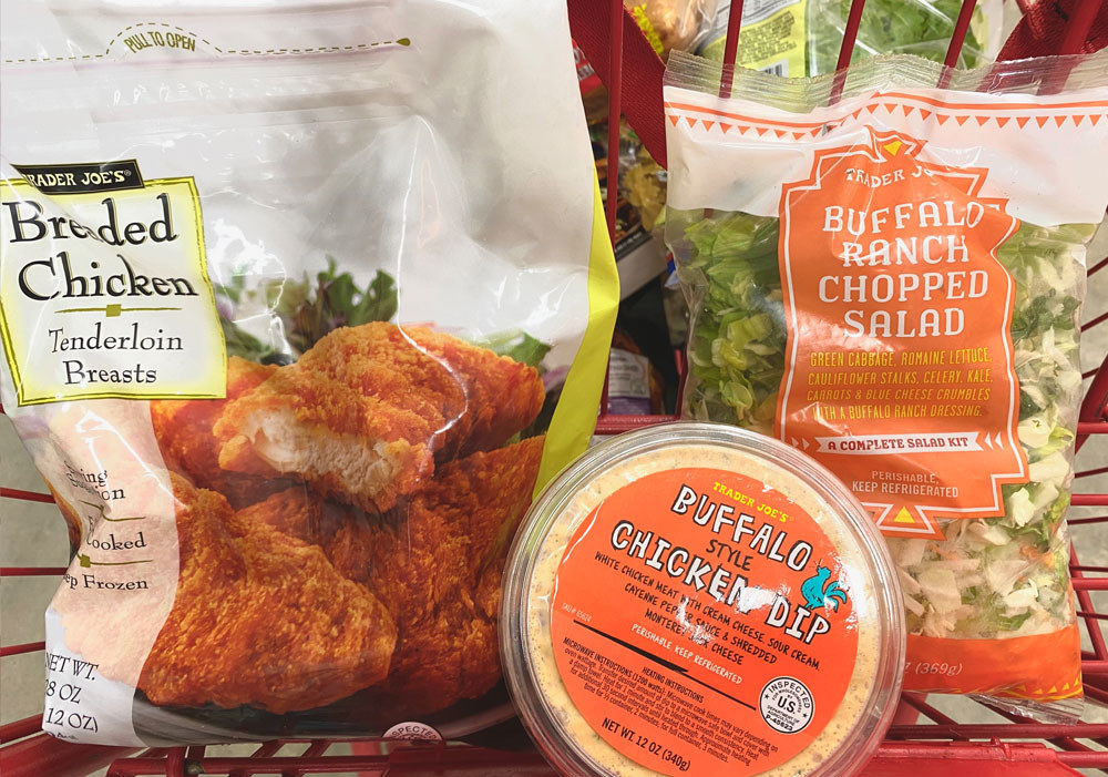 Breaded chicken tenders, buffalo style chicken dip, and buffalo ranch chopped salad in a shopping cart.