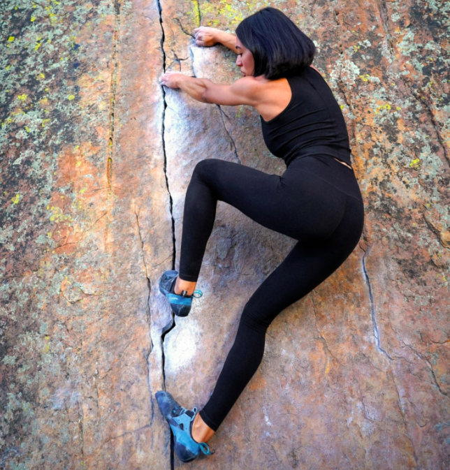 Model wears black performance tank with matching leggings while climbing the side of a rocky wall outdoors