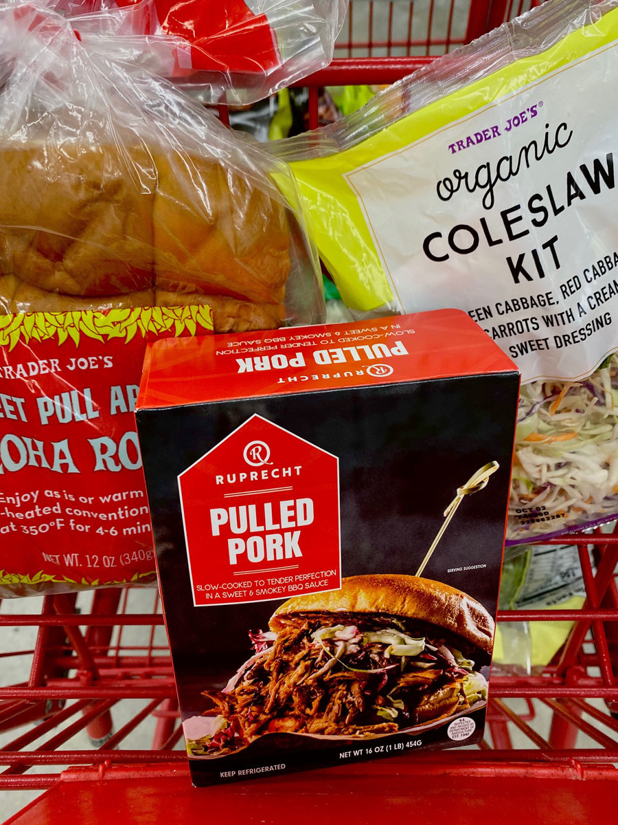 Pulled pork, aloha rolls, and coleslaw kit in a shopping cart.