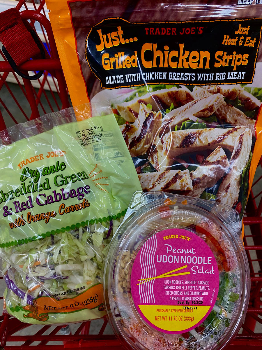 Peanut udon noodle salad, shredded cabbage, and frozen chicken breast strips in a shopping cart.