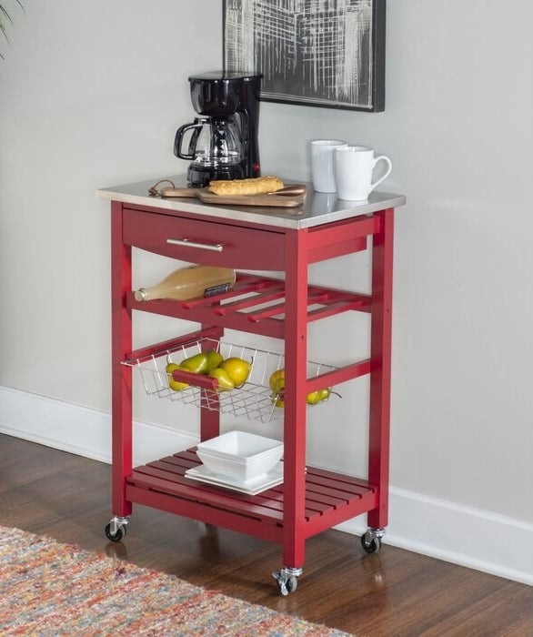 The red Haviland Kitchen Cart with Stainless Steel Top being used for storage in a kitchen