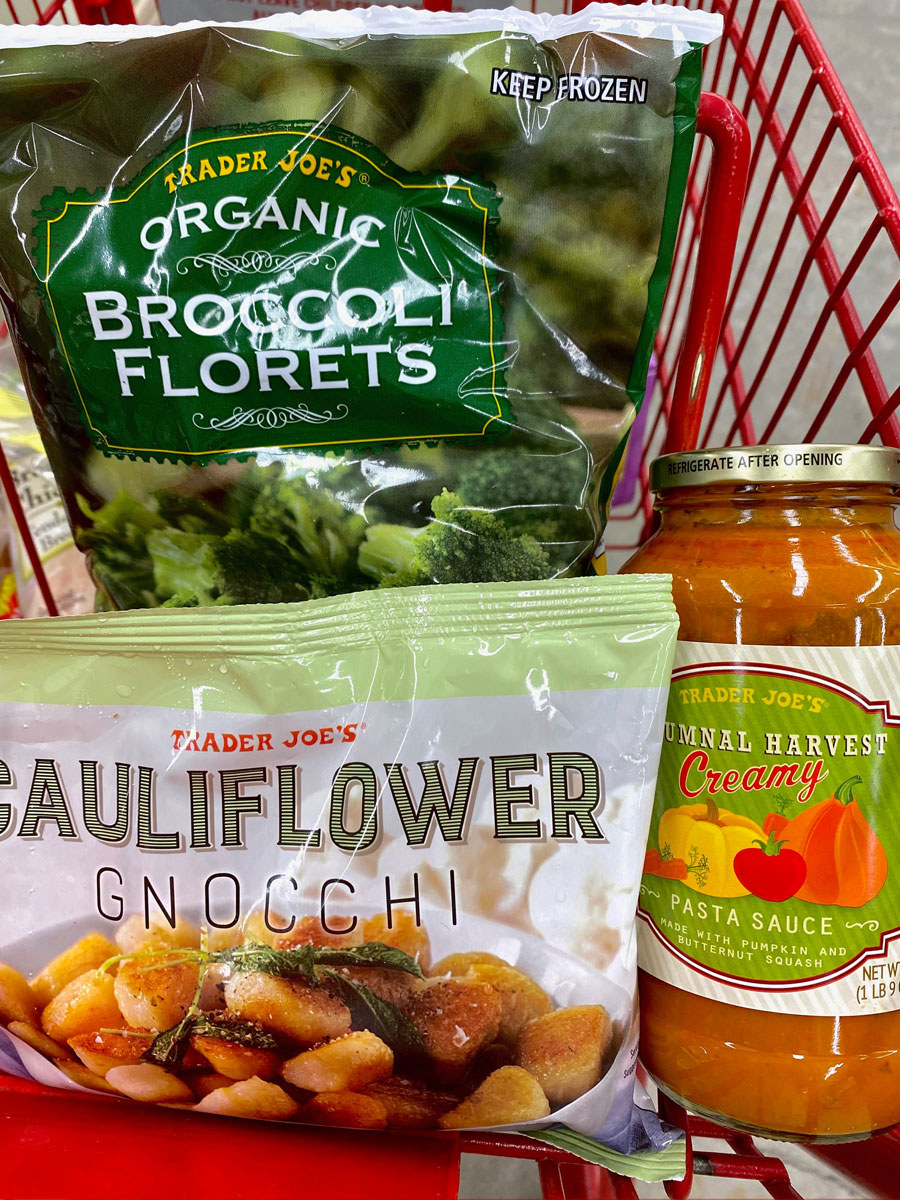Frozen broccoli florets, cauliflower gnocchi, and a jar of autumnal harvest pasta sauce in a shopping cart.