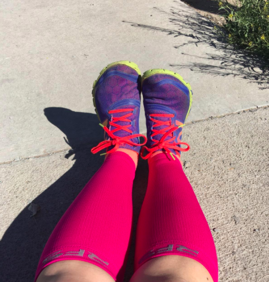 Reviewer wears pink calf compression sleeves with purple and neon green sneakers while sitting on the pavement