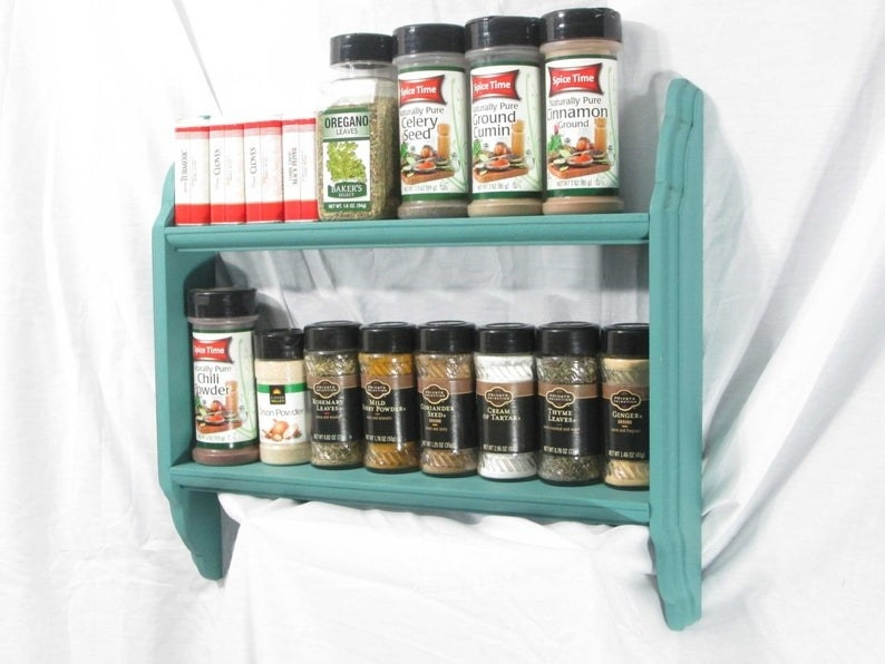 The teal mini mounted spice rack with spices on both of its shelves
