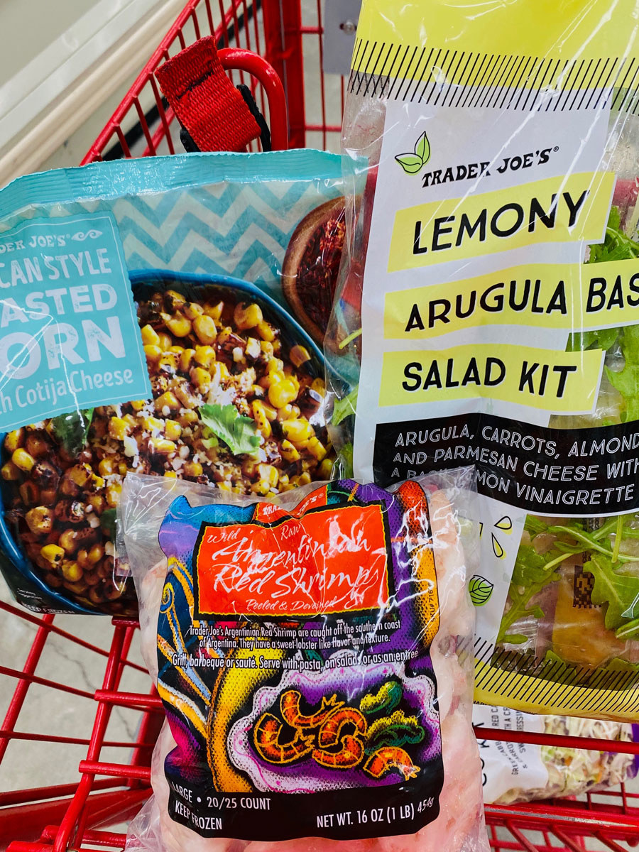 A bag of frozen roasted corn, frozen shrimp, and a lemony arugula salad kit in a shopping cart.