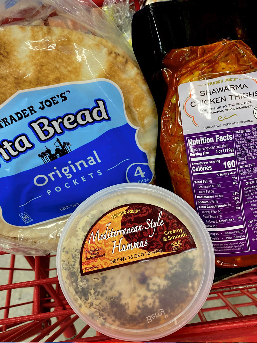 Mediterranean style hummus, pita bread, and shawarma chicken thighs in a shopping cart.