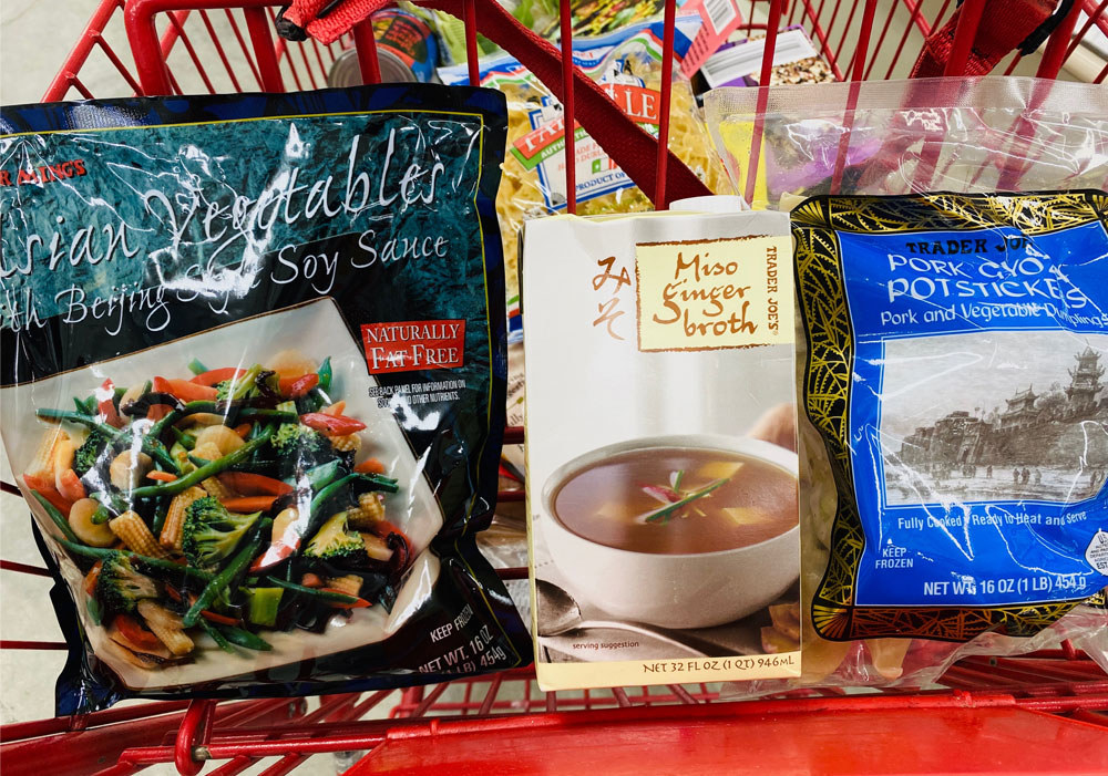 Stir fry vegetables, a carton of miso ginger soup, and frozen potstickers in a shopping cart.