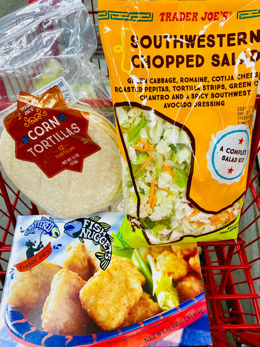 Frozen fish nuggets, southwestern chopped salad kit, and corn tortillas in a shopping cart.