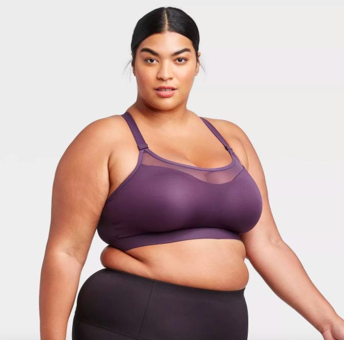 Model wears dark purple medium support sports bra with high-rise black leggings