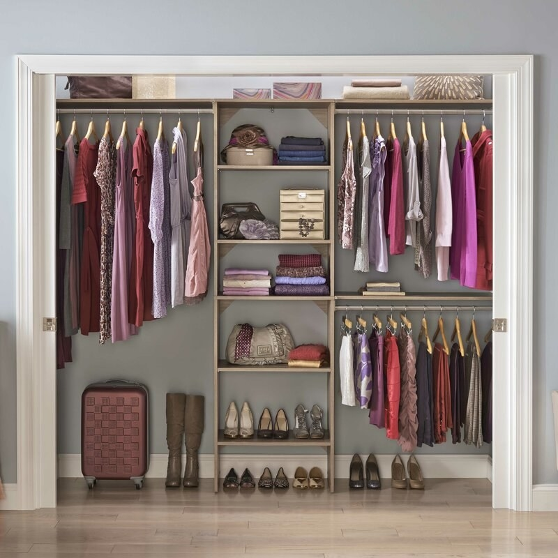 clothes, shoes, purses, a jewlery box, and a suitcase organized in a closet system with rails and shelves