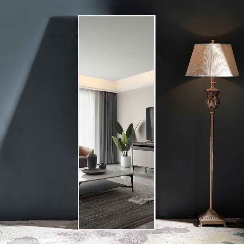 A full length mirror with a white border next to a floor lamp