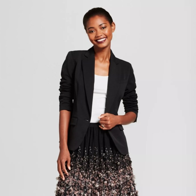 Model wearing a black blazer with a white shirt and skirt.