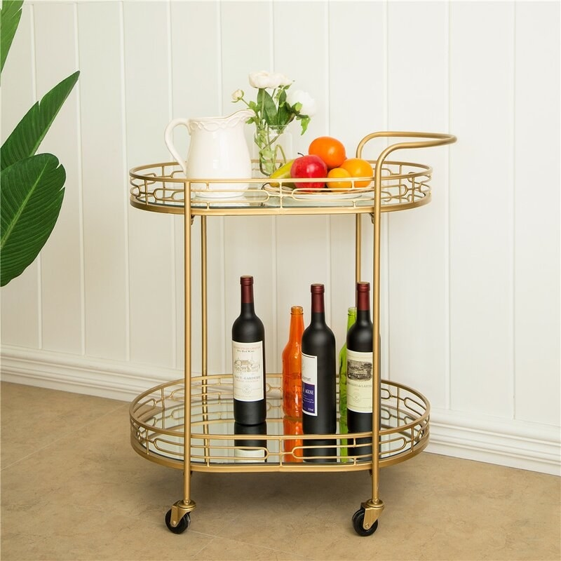 A gold bar cart with mirrored shelves holding fruit, a pitcher, and bottles of wine