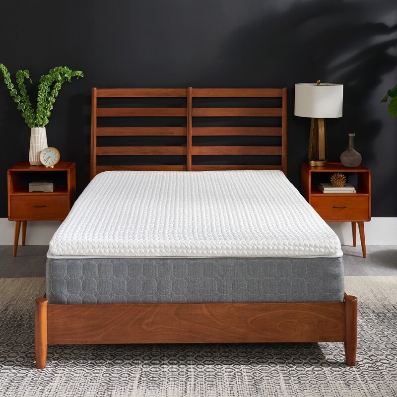 a white and grey mattress topper on a mattress atop a brown wooden bed frame