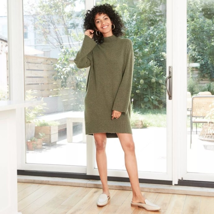 Model wearing green sweater dress with white loafers