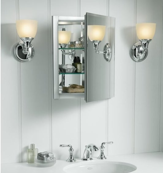 a mirrored medicine cabinet with adjustable glass shelves that are holding bathroom essentials. The medicine cabinet is hung above a bathroom sink