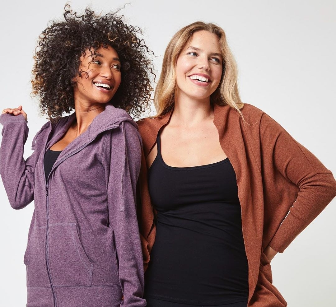 A model wearing a soft-looking, purple zip-up hoodie with drawstrings next to a model wearing a thinner, flowing brown cardigan over a black tank top