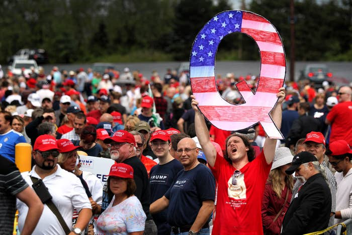 A person holds up a huge American flag–painted Q in a sea of red MAGA hats